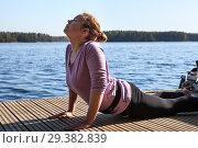 Занятие йогой и упражнение на растяжку на пирсе у озера. Стоковое фото, фотограф Кекяляйнен Андрей / Фотобанк Лори