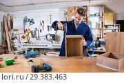 Купить «Male worker finishing to drill drawer», фото № 29383463, снято 7 ноября 2016 г. (c) Яков Филимонов / Фотобанк Лори