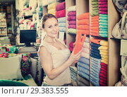 Купить «Young woman buying soft towels in textile store», фото № 29383555, снято 19 января 2019 г. (c) Яков Филимонов / Фотобанк Лори