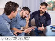 Купить «Three anxious men discussing on sofa», фото № 29393827, снято 10 января 2018 г. (c) Яков Филимонов / Фотобанк Лори