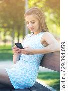 Купить «girl sitting on a bench and using phone in park», фото № 29394059, снято 8 июня 2017 г. (c) Яков Филимонов / Фотобанк Лори