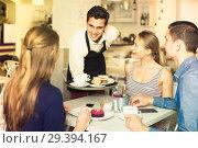 Купить «young smiling waiter bringing ordered dishes to friends in tearoom», фото № 29394167, снято 5 июня 2017 г. (c) Яков Филимонов / Фотобанк Лори