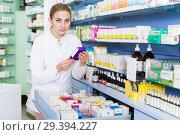 Купить «Woman pharmacist is holding medicines near shelves in apothecary», фото № 29394227, снято 26 марта 2018 г. (c) Яков Филимонов / Фотобанк Лори