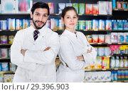 Купить «Portrait of two specialistes who are standing near shelves with medicines in pharmacy.», фото № 29396903, снято 28 февраля 2018 г. (c) Яков Филимонов / Фотобанк Лори