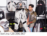 Купить «man is choosing new pants for motorbike in the moto store.», фото № 29396967, снято 1 сентября 2017 г. (c) Яков Филимонов / Фотобанк Лори