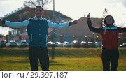Купить «Young people in sport costumes warming up in park. Beautiful sunlight», видеоролик № 29397187, снято 7 августа 2020 г. (c) Константин Шишкин / Фотобанк Лори