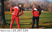 Купить «Two young woman in sport costumes are starting warming up in park», видеоролик № 29397539, снято 23 июля 2019 г. (c) Константин Шишкин / Фотобанк Лори