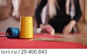 Купить «Young woman at sewing factory. A woman making sketches on the cloth. Sewing thread in focus», видеоролик № 29400843, снято 20 ноября 2018 г. (c) Константин Шишкин / Фотобанк Лори