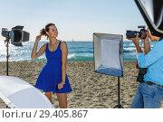 Купить «Professional photo shooting outdoors. smiling female model posing to photographer on sunny beach», фото № 29405867, снято 5 октября 2018 г. (c) Яков Филимонов / Фотобанк Лори
