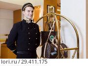 Купить «Young man in uniform serving in hotel», фото № 29411175, снято 6 июля 2017 г. (c) Ekaterina Demidova / Фотобанк Лори