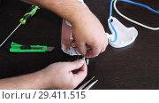 Купить «Мастер ремонтирует утюг. Мужские руки крупным планом», видеоролик № 29411515, снято 8 ноября 2017 г. (c) Олег Хархан / Фотобанк Лори