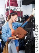 Купить «Girl buying handbag in fashion shop», фото № 29412243, снято 15 сентября 2016 г. (c) Яков Филимонов / Фотобанк Лори