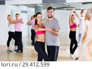 Купить «Smiling young couples dancing of partner dance», фото № 29412599, снято 9 октября 2017 г. (c) Яков Филимонов / Фотобанк Лори