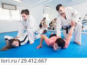 Купить «trainees sparring in pairs to practice new holds in taekwondo class», фото № 29412667, снято 8 апреля 2017 г. (c) Яков Филимонов / Фотобанк Лори