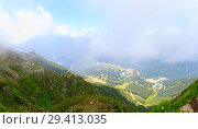 Panorama of the mountains and Aibga Ridge with cable car and low clouds. Mountains near the ski resort of Rosa Khutor in Krasnaya Polyana. Sochi, Russia. Стоковое фото, фотограф Mikhail Starodubov / Фотобанк Лори