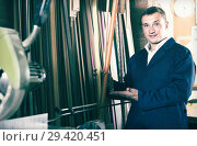 Купить «portrait of man in uniform choosing framing moulding in studio», фото № 29420451, снято 19 января 2019 г. (c) Яков Филимонов / Фотобанк Лори