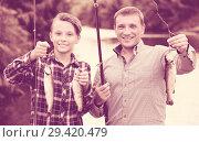 Купить «Man with teenager boy showing catch fish», фото № 29420479, снято 10 декабря 2018 г. (c) Яков Филимонов / Фотобанк Лори