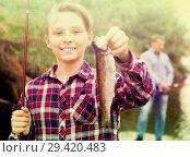 Купить «Boy holding catch freshwater fish in hands», фото № 29420483, снято 18 января 2019 г. (c) Яков Филимонов / Фотобанк Лори