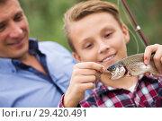 Купить «Smiling teenage boy catching on hook fish», фото № 29420491, снято 18 января 2019 г. (c) Яков Филимонов / Фотобанк Лори