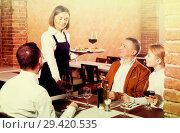 Купить «Female waiter carrying order for visitors», фото № 29420535, снято 16 декабря 2018 г. (c) Яков Филимонов / Фотобанк Лори