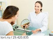 Купить «Woman client checking result of beauty procedures», фото № 29420835, снято 26 апреля 2019 г. (c) Яков Филимонов / Фотобанк Лори