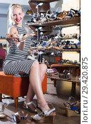 Купить «Glad young woman choosing two pairs of new shoes», фото № 29420875, снято 24 августа 2019 г. (c) Яков Филимонов / Фотобанк Лори