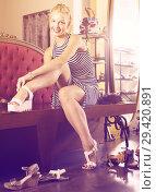Купить «Girl customer trying on pair of shoes in fashion shop», фото № 29420891, снято 9 декабря 2018 г. (c) Яков Филимонов / Фотобанк Лори