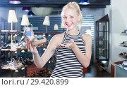 Купить «Young female customer showing sandals in hands», фото № 29420899, снято 15 декабря 2018 г. (c) Яков Филимонов / Фотобанк Лори
