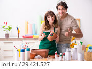 Купить «Couple decorating pots in workshop during class», фото № 29421527, снято 11 июля 2018 г. (c) Elnur / Фотобанк Лори