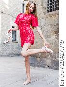 Купить «portrait of young smiling adult girl in evening apparel remove sandals in outdoor», фото № 29427719, снято 24 июня 2017 г. (c) Яков Филимонов / Фотобанк Лори