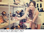 Купить «Cheerful woman choosing pair of summer shoes», фото № 29427767, снято 9 декабря 2018 г. (c) Яков Филимонов / Фотобанк Лори