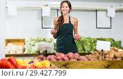 Купить «Female seller wearing apron working on fruit market», фото № 29427799, снято 18 июля 2019 г. (c) Яков Филимонов / Фотобанк Лори