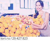 Купить «Positive young woman buying oranges», фото № 29427823, снято 29 мая 2020 г. (c) Яков Филимонов / Фотобанк Лори