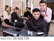 Купить «Hairdresser finished haircut of pleased man client», фото № 29428135, снято 5 марта 2018 г. (c) Яков Филимонов / Фотобанк Лори