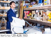 Купить «Sellerman in uniform is putting bags on the shelves in the building store.», фото № 29428183, снято 26 июля 2017 г. (c) Яков Филимонов / Фотобанк Лори