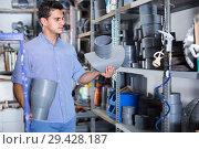 Купить «concentrated male is choosing plastic trumpet in the plumbing department in store», фото № 29428187, снято 26 июля 2017 г. (c) Яков Филимонов / Фотобанк Лори