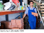 Купить «Craftsman is choosing tiles», фото № 29428199, снято 26 июля 2017 г. (c) Яков Филимонов / Фотобанк Лори