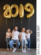 Купить «Happy family holding sign 2019 made of golden balloons for new year on black background.», фото № 29428687, снято 9 ноября 2018 г. (c) Женя Канашкин / Фотобанк Лори