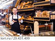 Купить «Baker offers white crisp bread», фото № 29431499, снято 26 января 2017 г. (c) Яков Филимонов / Фотобанк Лори