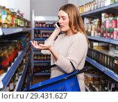 Купить «Female talking by phone in grocery», фото № 29431627, снято 11 апреля 2018 г. (c) Яков Филимонов / Фотобанк Лори