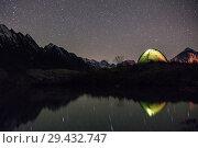 Купить «Night view of illuminated tent near lake», фото № 29432747, снято 13 октября 2017 г. (c) Донцов Евгений Викторович / Фотобанк Лори