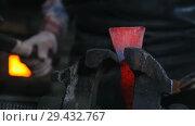 Купить «Blacksmith getting a red-hot top of the axe. The detail in the clamp», видеоролик № 29432767, снято 20 ноября 2018 г. (c) Константин Шишкин / Фотобанк Лори
