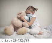 Купить «A child in a medical mask on the bed with a big toy bear», фото № 29432799, снято 16 ноября 2018 г. (c) Ирина Козорог / Фотобанк Лори