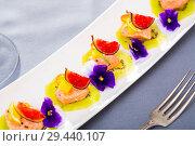 Купить «Ceviche from red trout on plate with cumquat, kiwi, figs and flower», фото № 29440107, снято 19 апреля 2019 г. (c) Яков Филимонов / Фотобанк Лори