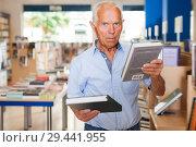 Купить «pensioner male customer visiting bookshop in search of interesting fiction», фото № 29441955, снято 11 июня 2018 г. (c) Яков Филимонов / Фотобанк Лори