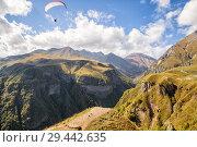 Купить «Paragliders fly over beautiful gorge in Caucasus, Georgia», фото № 29442635, снято 24 сентября 2018 г. (c) Юлия Бабкина / Фотобанк Лори