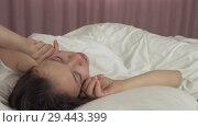 Купить «Beautiful teen girl wakes up in bed and smiles stock footage video», видеоролик № 29443399, снято 7 ноября 2018 г. (c) Юлия Машкова / Фотобанк Лори