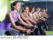 Купить «Girls during workout on stationary bicycle in fitness gym», фото № 29450027, снято 26 июля 2017 г. (c) Яков Филимонов / Фотобанк Лори