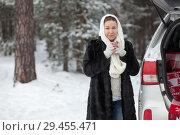 Купить «Young European woman standing near her car and holding tea mug in hands at winter season, copyspace», фото № 29455471, снято 21 января 2018 г. (c) Кекяляйнен Андрей / Фотобанк Лори