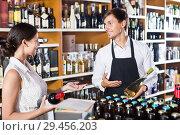 Купить «Seller helping woman customer with bottle of wine», фото № 29456203, снято 19 декабря 2018 г. (c) Яков Филимонов / Фотобанк Лори